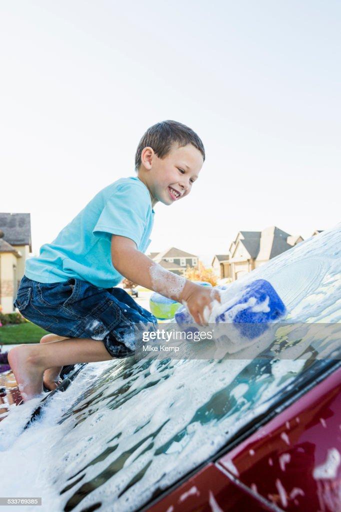 Caucasian boy washing car windshield : Foto stock