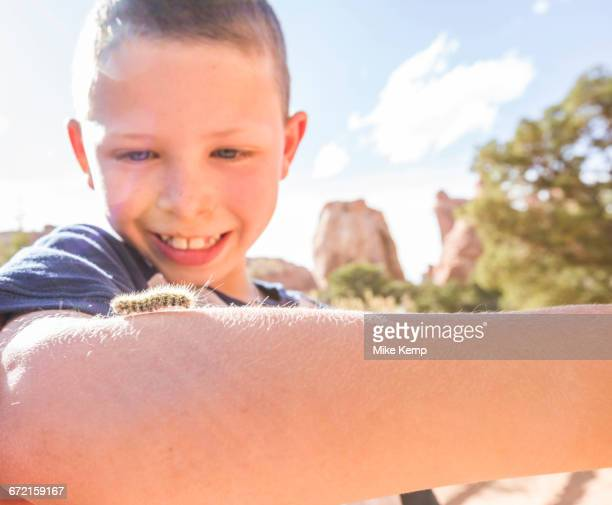 Caucasian boy watching caterpillar crawl on arm