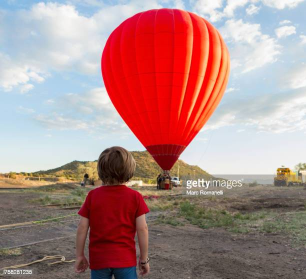 caucasian boy watching distant hot air balloon - hot air balloon stock pictures, royalty-free photos & images
