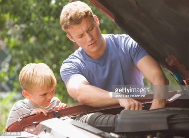 Caucasian boy watching father work on car engine
