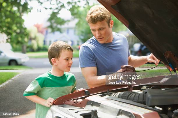 caucasian boy watching father work on car engine - oil change stock pictures, royalty-free photos & images