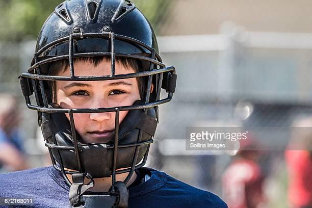 Caucasian boy wearing baseball catchers mask