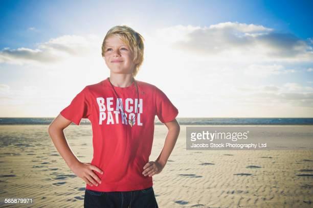 Caucasian boy wearing beach patrol shirt on beach