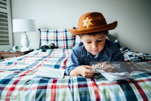 Caucasian boy wearing cowboy costume reading booklet on bed