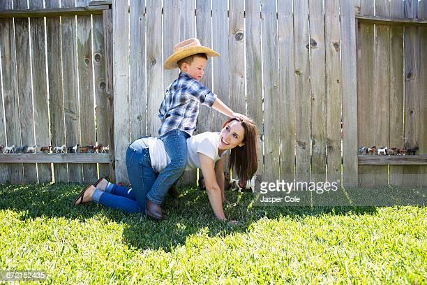 Caucasian boy wearing cowboy hat sitting horseback on mother