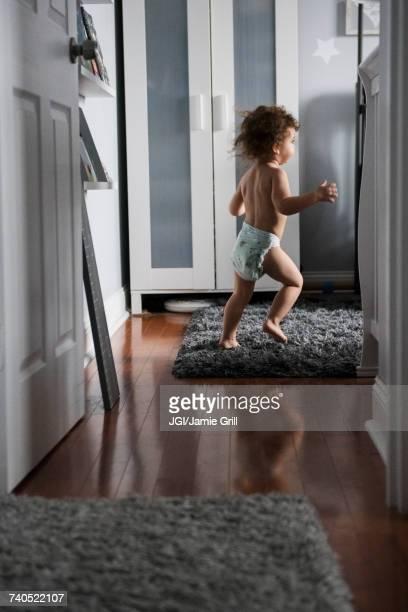 caucasian boy wearing diaper running in corridor - diaper kids stock-fotos und bilder