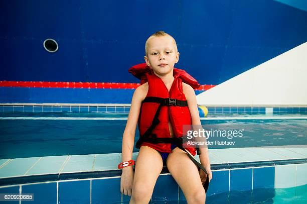 Caucasian boy wearing lifejacket at swimming pool