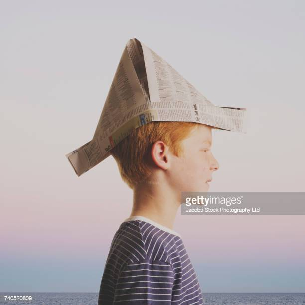 caucasian boy wearing paper hat near ocean - hat stock pictures, royalty-free photos & images