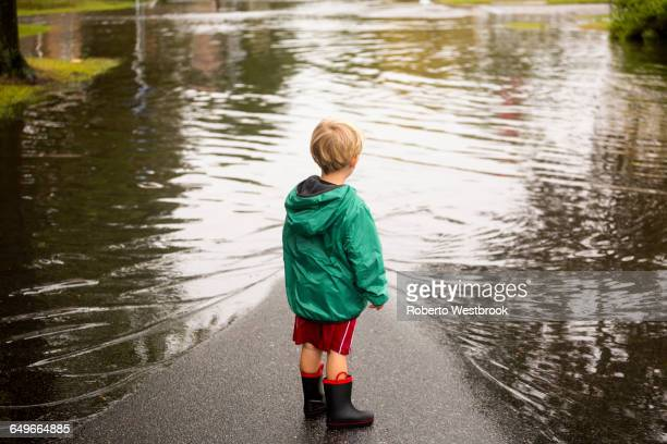 caucasian boy wearing puddles near flood - flooding stock photos and pictures
