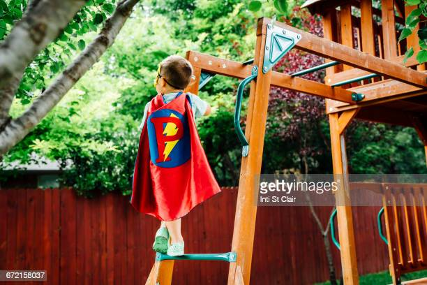 caucasian boy wearing superhero costume climbing on backyard playground - letter p stock pictures, royalty-free photos & images