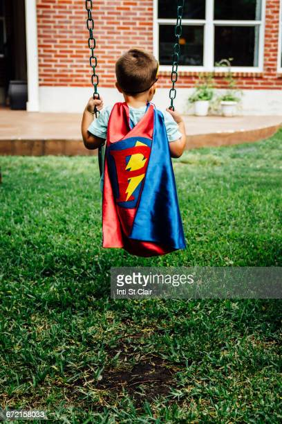 caucasian boy wearing superhero costume on swing - letter p stock pictures, royalty-free photos & images