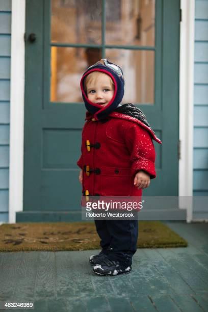 Caucasian boy wearing winter coat on porch