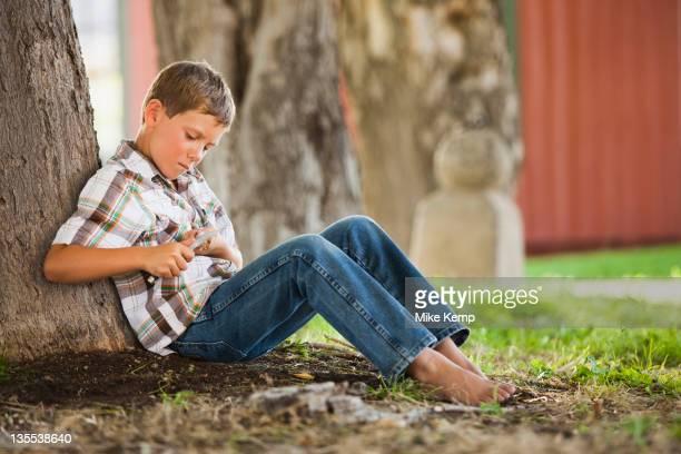 Caucasian boy whittling stick