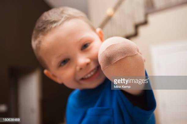 caucasian boy with bandage on elbow - healing wound stock pictures, royalty-free photos & images