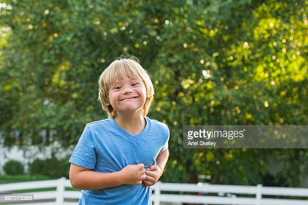 Caucasian boy with Down Syndrome smiling outdoors