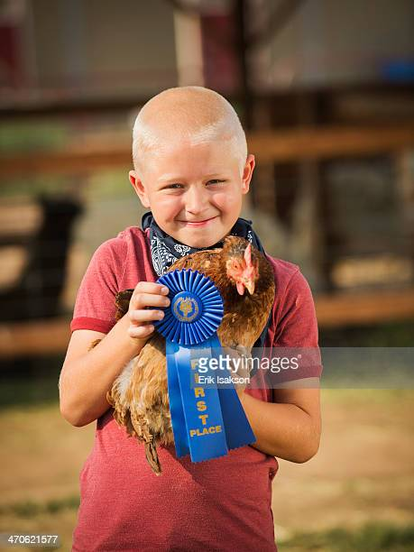 Caucasian boy with prize winning chicken on farm