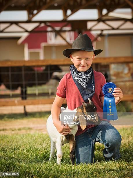 Caucasian boy with prize winning goat on farm