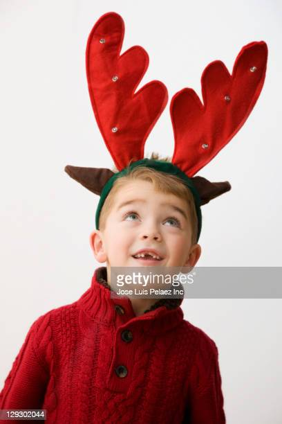 Caucasian boy with reindeer antlers headband on his head