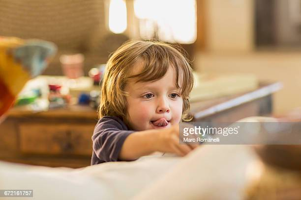 Caucasian boy with tongue out playing with toy