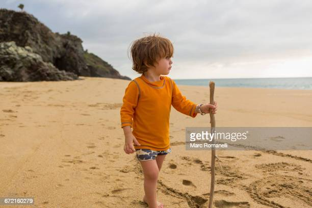 Caucasian boy with walking stick on beach