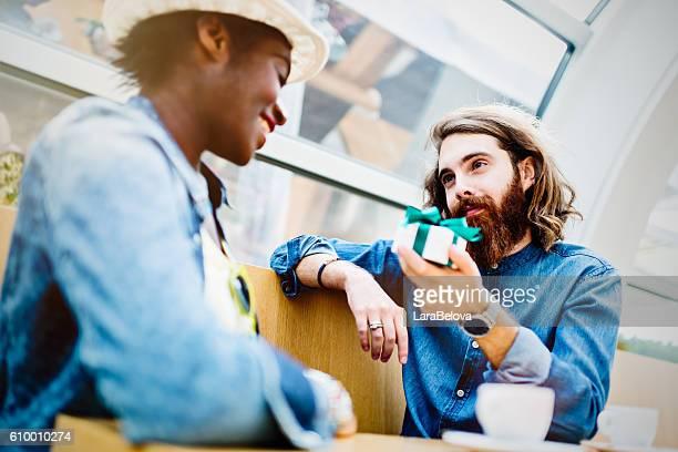 Caucasian boyfriend giving present to his African girlfriend