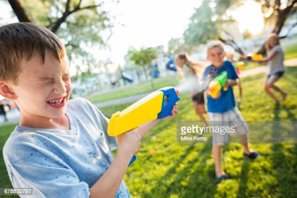 Caucasian boys and girls playing with squirt guns