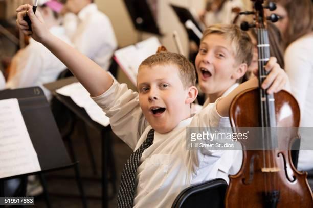 Caucasian boys celebrating in music class