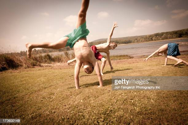 Caucasian boys doing cartwheels in grass
