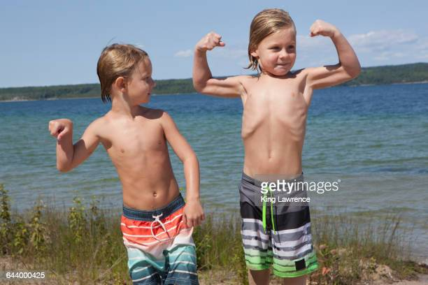 caucasian boys flexing muscles on beach - spieren spannen stockfoto's en -beelden