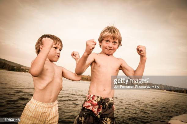 caucasian boys flexing muscles on wooden dock - zwembroek stockfoto's en -beelden