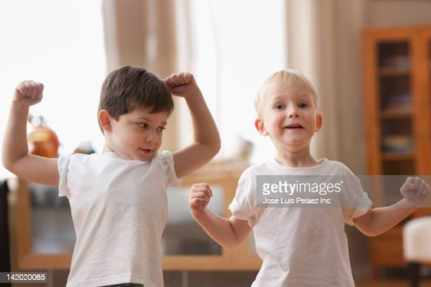 Caucasian boys flexing muscles