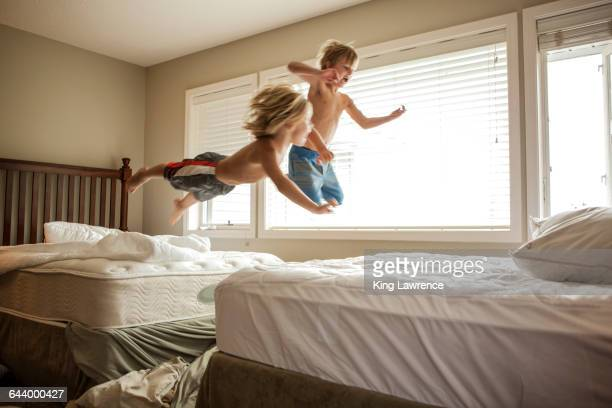 Caucasian boys jumping on beds
