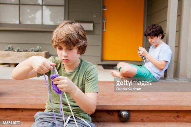 caucasian boys knitting on patio - stricken stock-fotos und bilder