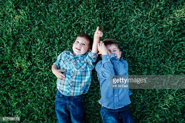 Caucasian boys laying in grass playing