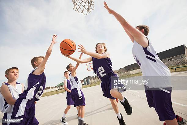 caucasian boys playing basketball on court - basketbal teamsport stockfoto's en -beelden