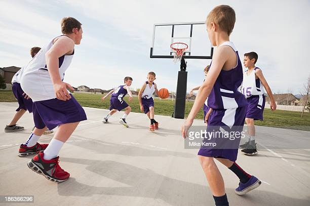 Caucasian boys playing basketball on court