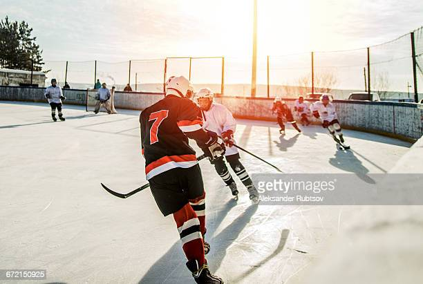 caucasian boys playing ice hockey outdoors - ice hockey stock pictures, royalty-free photos & images