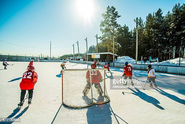 caucasian boys playing ice hockey outdoors - difensore hockey su ghiaccio foto e immagini stock