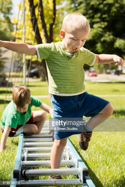 Caucasian boys playing with ladder
