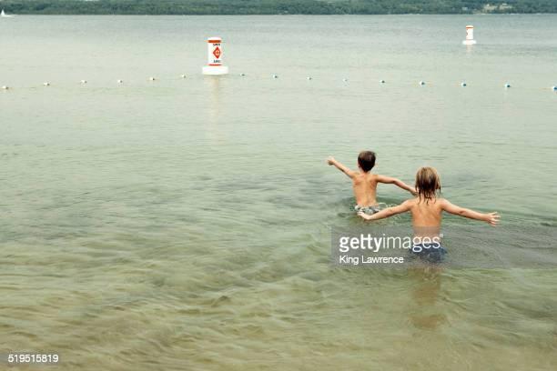 Caucasian boys swimming in lake