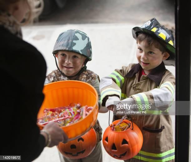 Caucasian boys trick or treating on Halloween