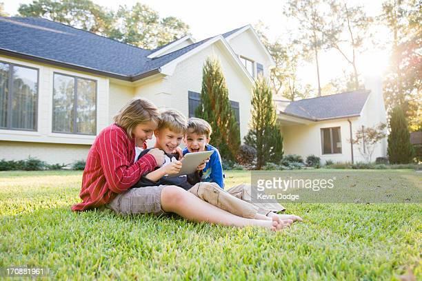 Caucasian boys using digital tablet on lawn