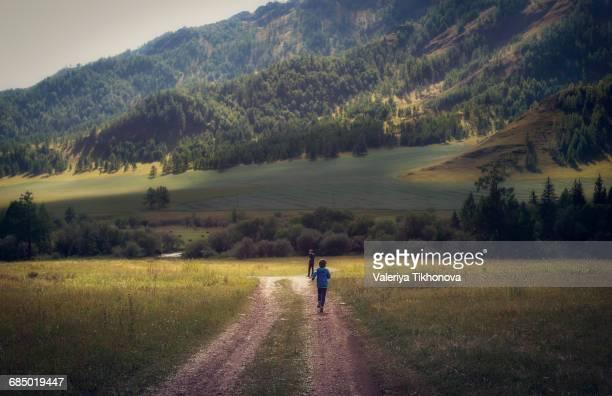 Caucasian boys walking on remote path