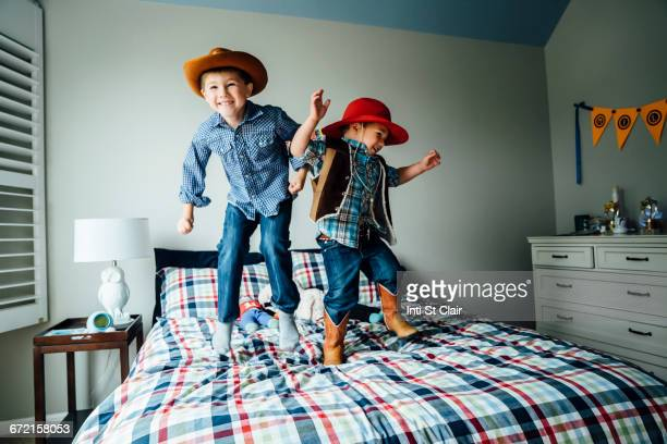Caucasian boys wearing cowboy costumes jumping on bed