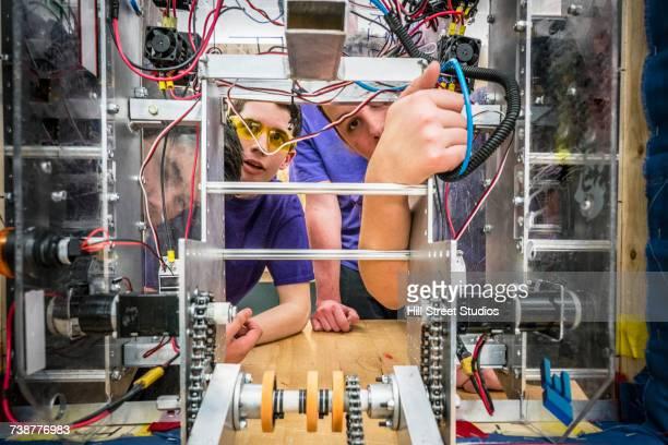 Caucasian boys wiring robotics in school