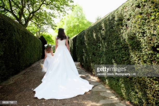 caucasian bride and flower girl walking in garden - bride stock pictures, royalty-free photos & images