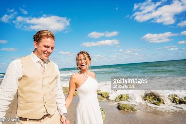Caucasian bride and groom holding hands on beach