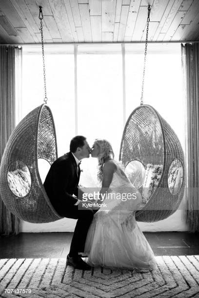 Caucasian bride and groom kissing in hanging chairs