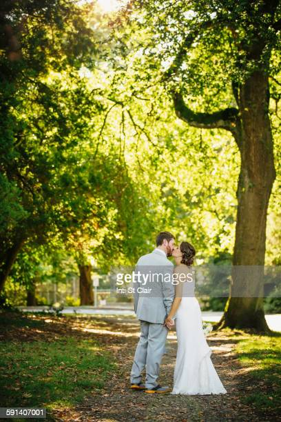 Caucasian bride and groom kissing on dirt path