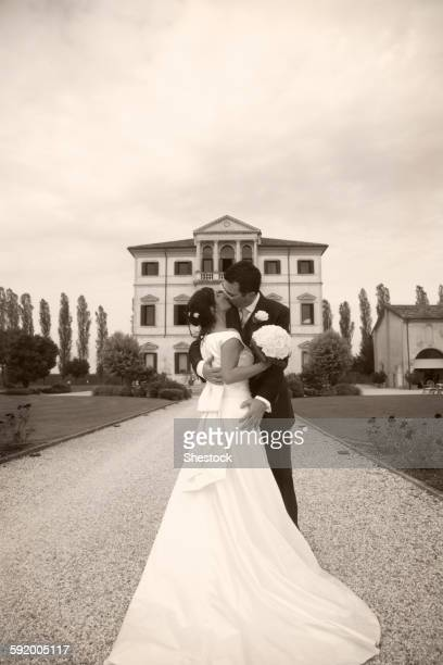 caucasian bride and groom kissing on gravel path - marriage stock pictures, royalty-free photos & images